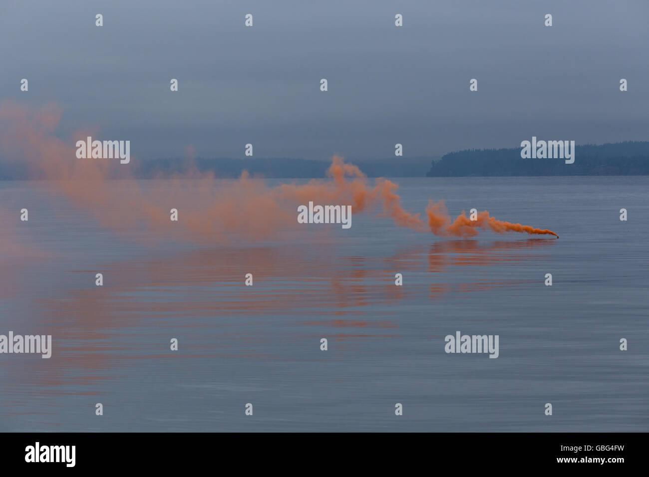Orange smoke on the water - Stock Image