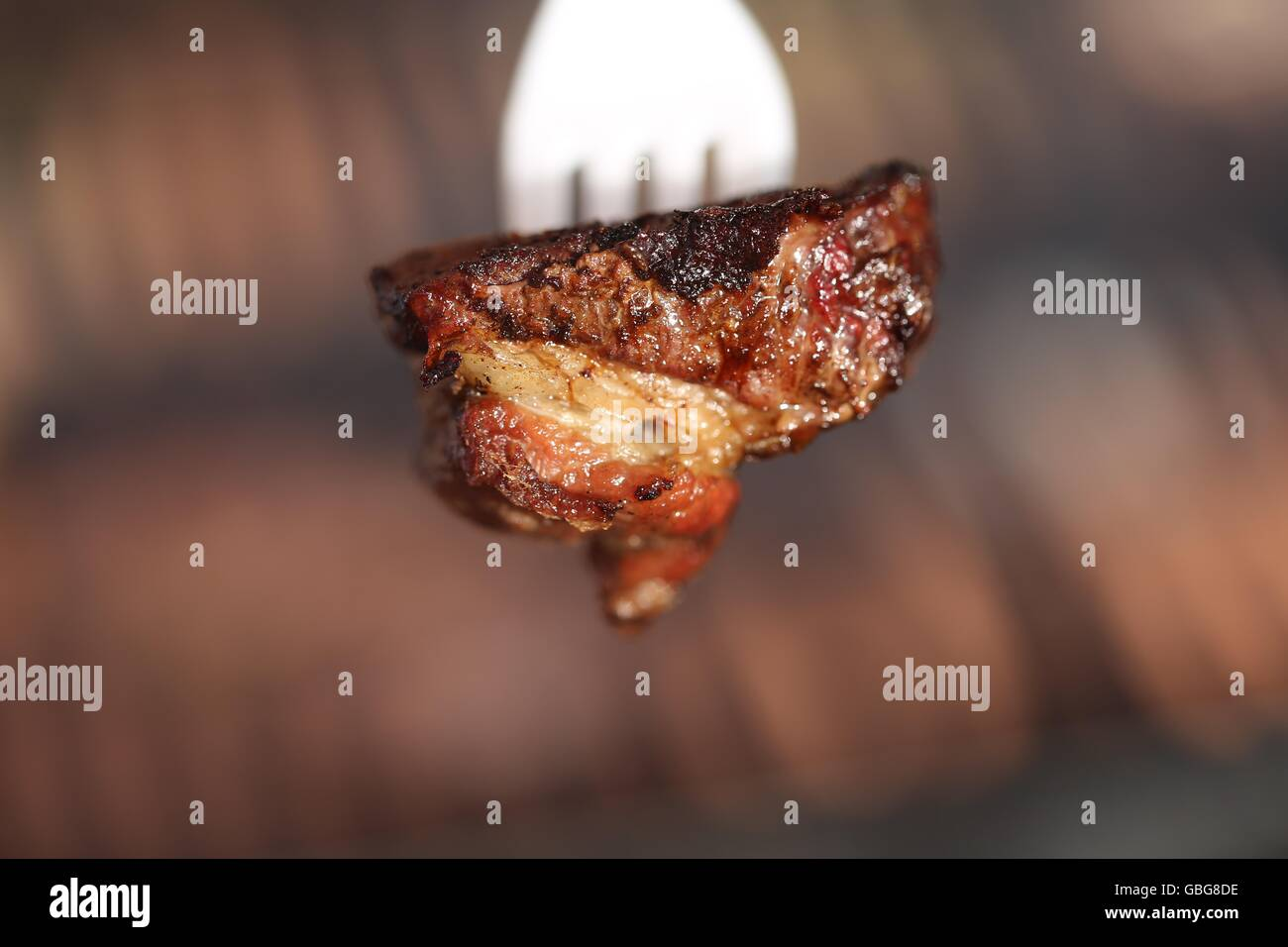 Piece of Rare Beef Meat on a Plastic Fork. Piece of sinta steak on a disposable fork, close up. Red meat stuck on - Stock Image