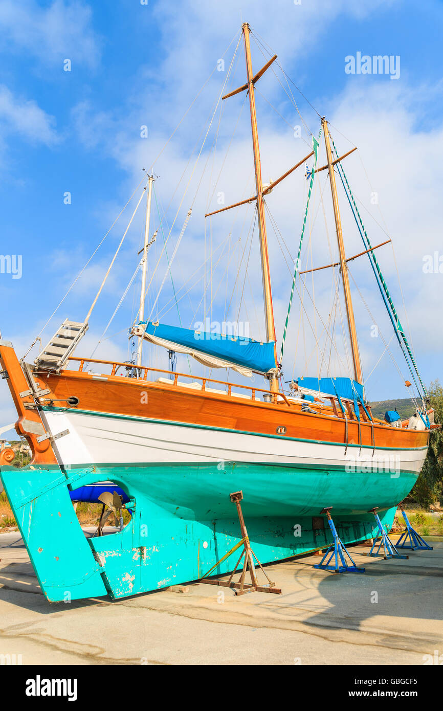 Traditional wooden sail boat in shipyard of small Greek marina, Samos island, Greece - Stock Image