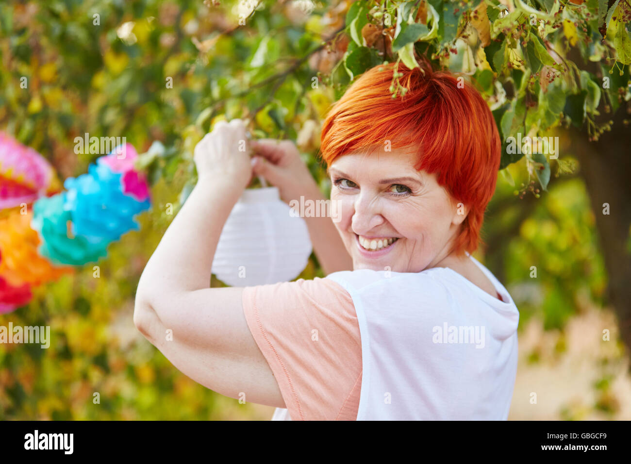 Senior woman decorating for a party in the park - Stock Image