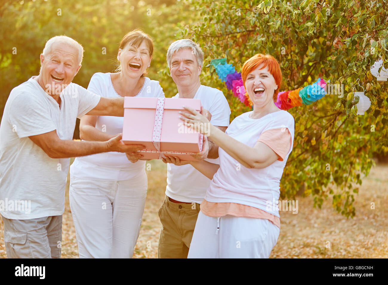 Seniors laughing and smiling with a birthday present at a party - Stock Image