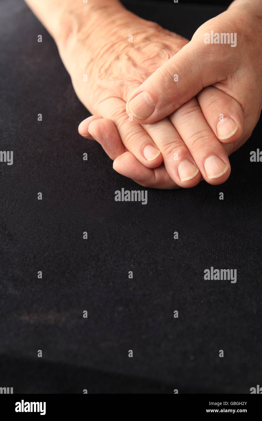 Senior man grasps his aching fingers, copy space included - Stock Image