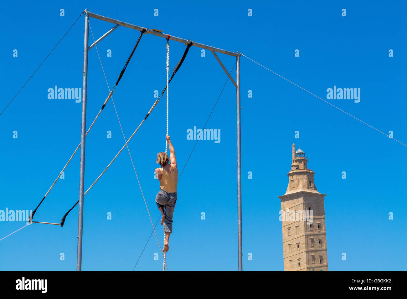 Low Angle View Of Gymnast Performing On Rope Against Clear Blue Sky - Stock Image