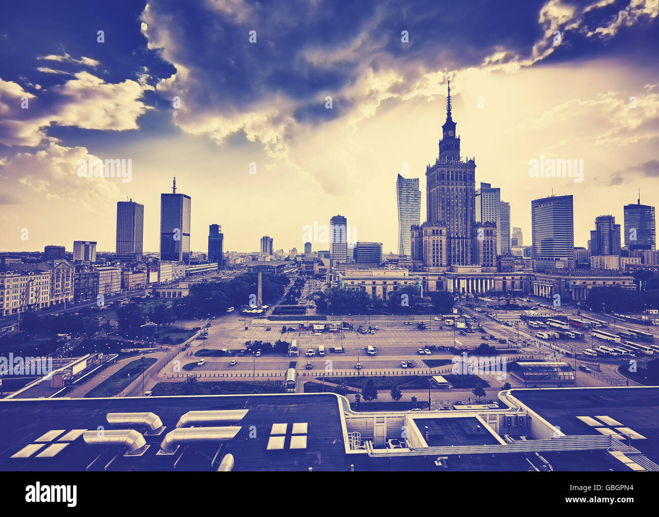 Old grainy film style Warsaw downtown with Palace of Culture and Science and skyscrapers at sunset, Poland. - Stock Image