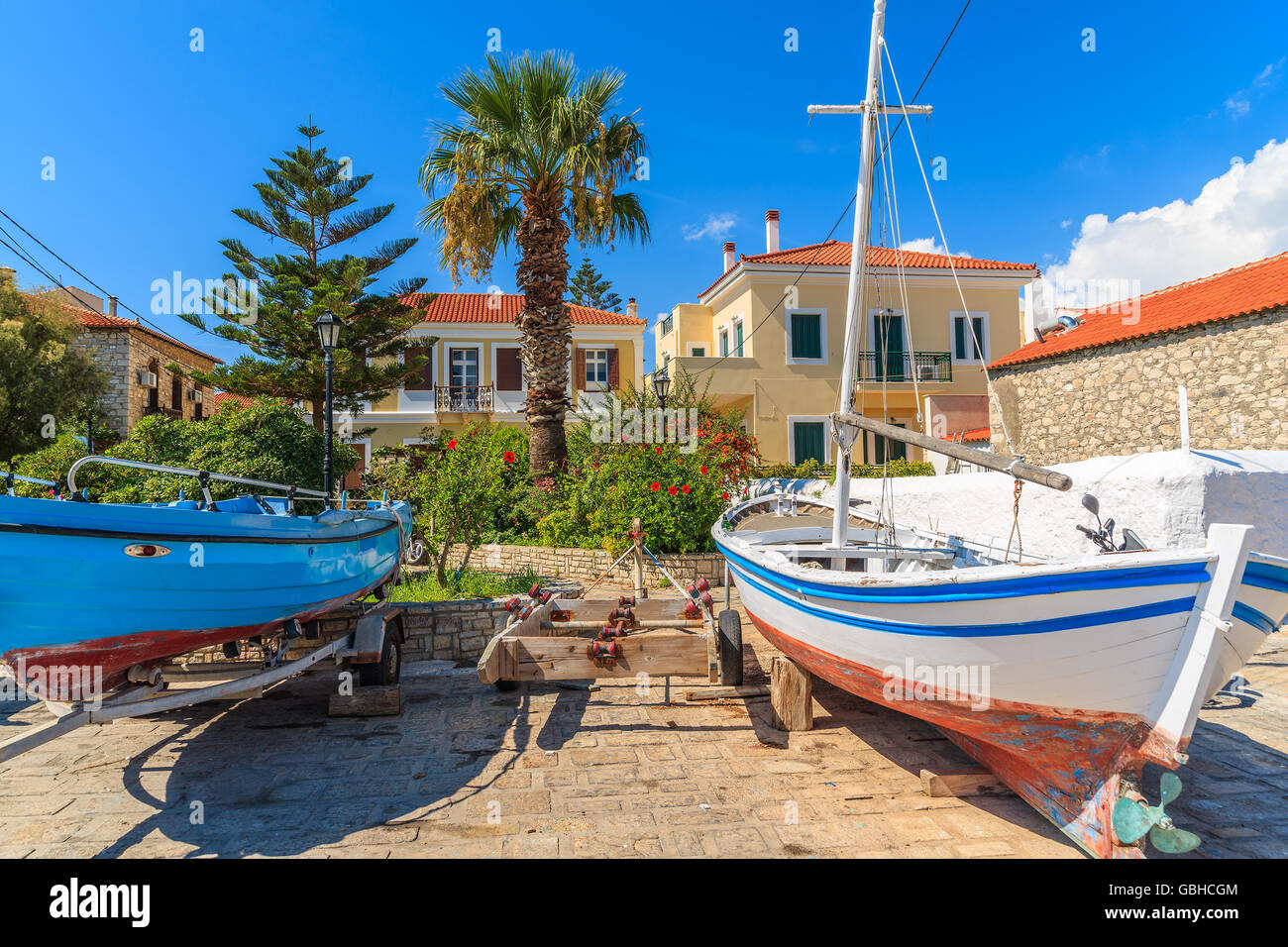 Fishing boats in dock of Pythagorion port with traditional colourful Greek houses in background, Samos island, Greece Stock Photo