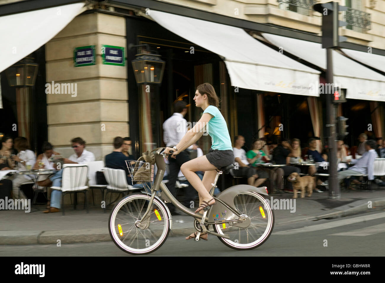 A woman rides a Velib' bicycle past a café terrace in Paris, France, 15th July 2007. - Stock Image