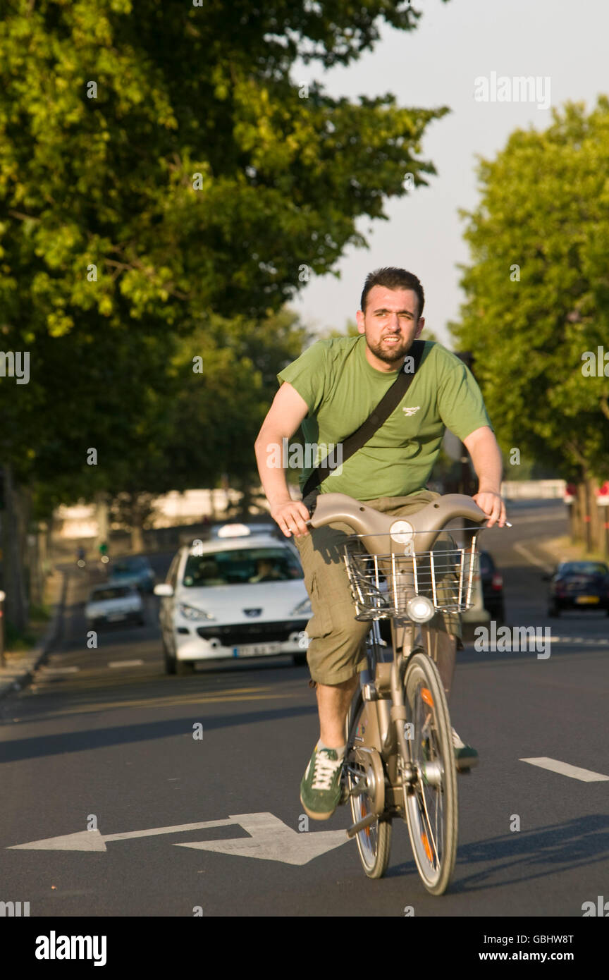 A man rides a Velib' bicycle in Paris, France, 15th July 2007. - Stock Image