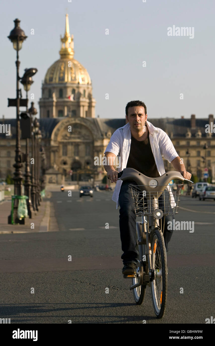 A man rides a Velib' bicycle across the Esplanade des Invalides in Paris, France, 15th July 2007. - Stock Image