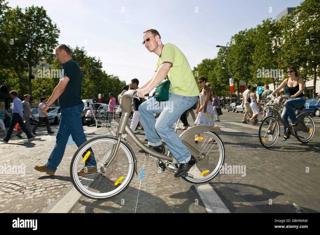 A man rides a Velib' bicycle across the Champs-Elysees in Paris, France, 15th July 2007. - Stock Image