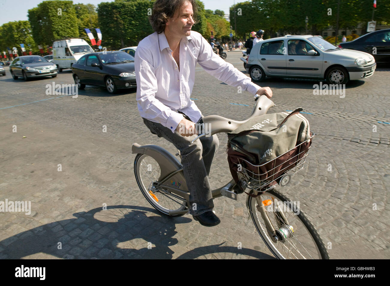 A man rides a Velib' bicycle down the Champs-Elysees in Paris, France, 15th July 2007. - Stock Image