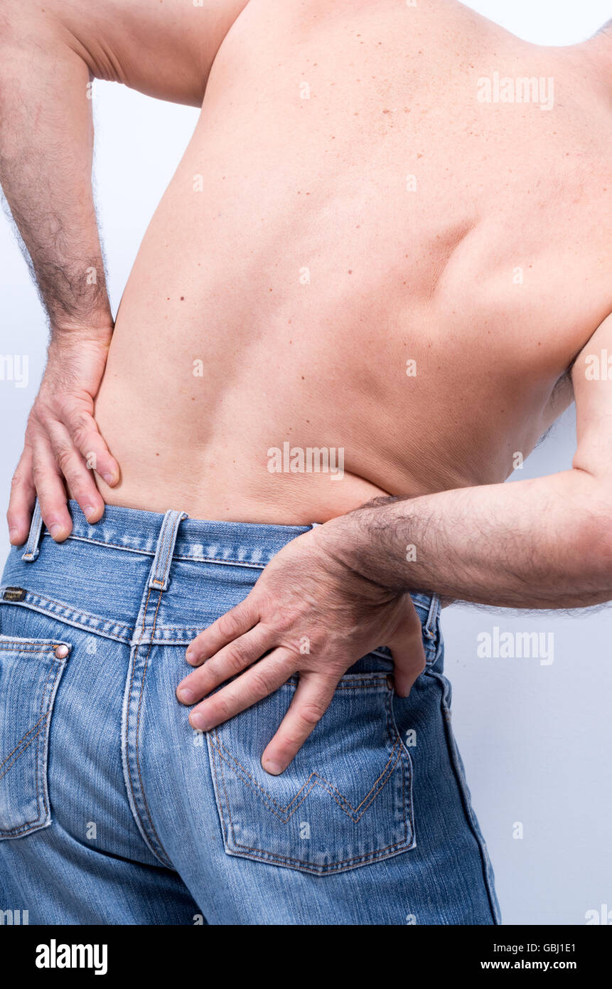 middle-aged man with severe pain in the lumbar region pushes them with the hands - Stock Image