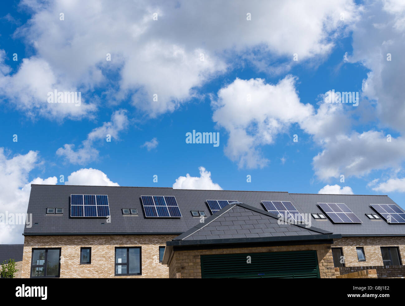 Domestic solar panels on the rooftop of newly built houses - Stock Image
