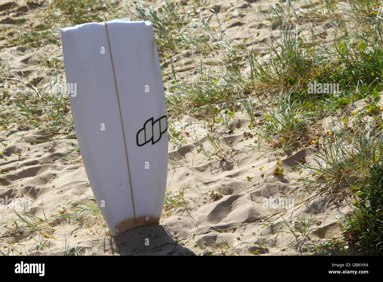 A section of a broken surfboard stuck into the beach sand after breaking in the big surf at Sandon Point, Bulli, - Stock Image
