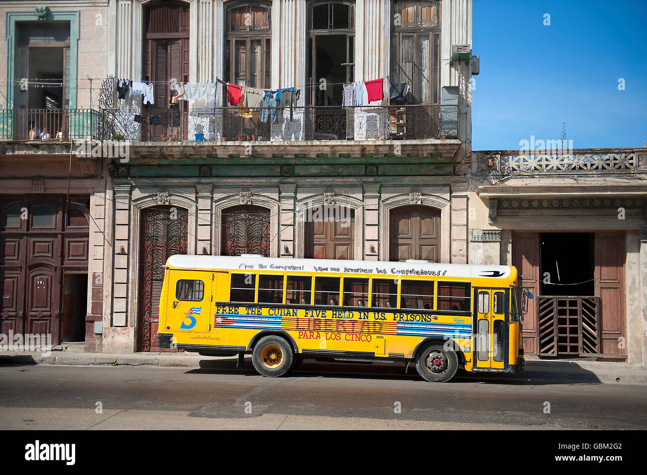 yellow school bus under clothesline with clothes hanging to dry - Stock Image