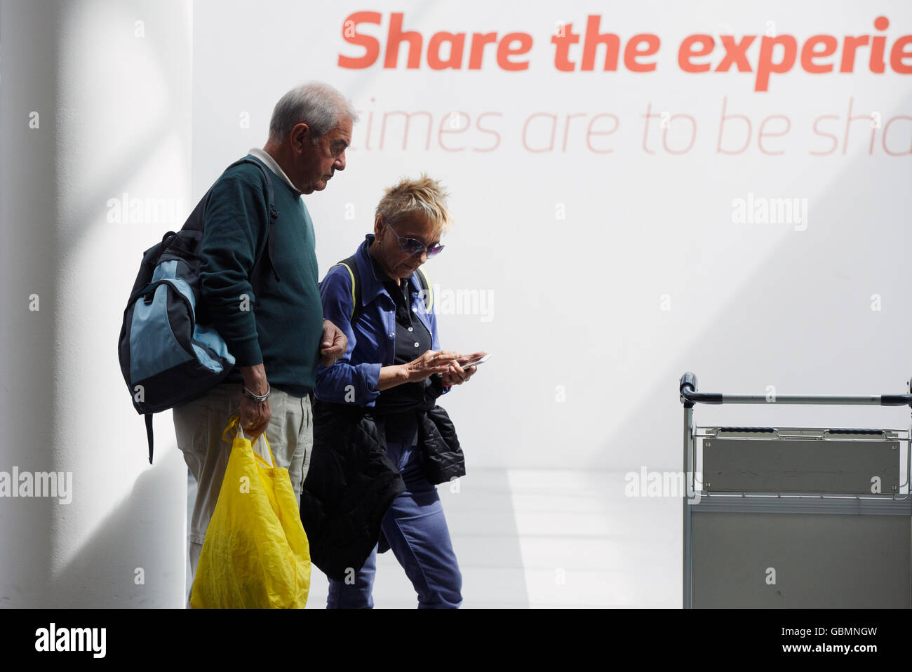 A couple using a smart phone, Keflavik International Airport, Keflavik, Iceland - Stock Image