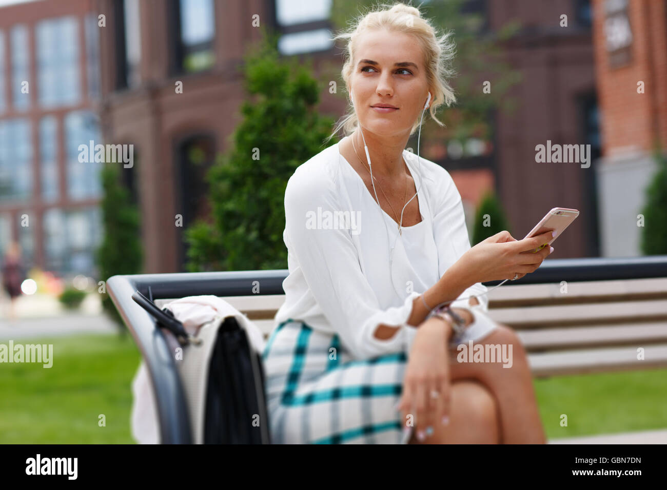 Tired pensive young woman leaning on sculpture outdoors - Stock Image
