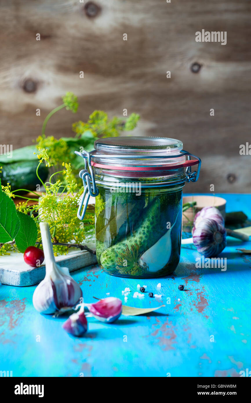 Making pickled cucumbers, homemade pickles in jar on rustic wooden table - Stock Image
