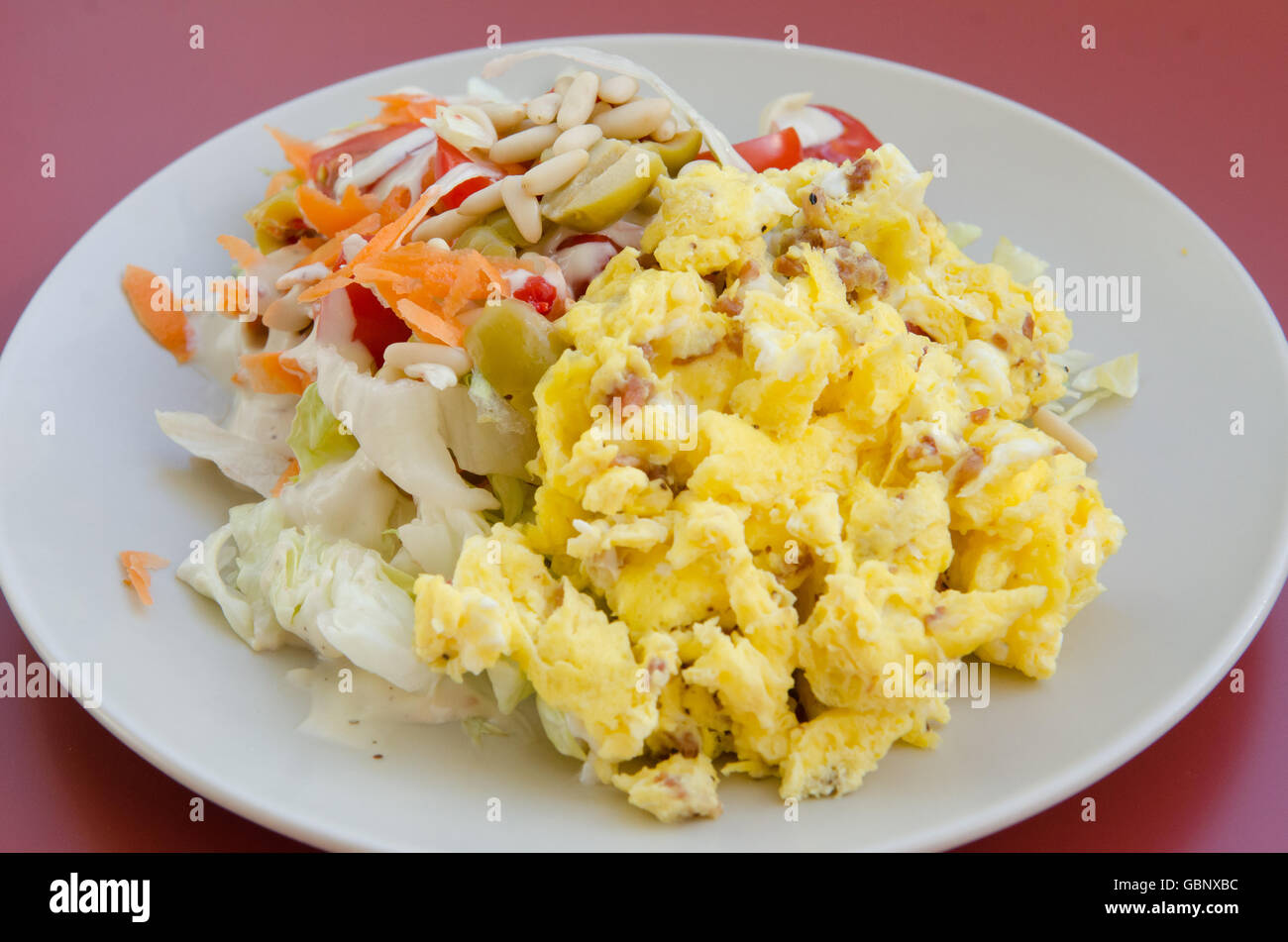 Plated scramble eggs and salad with pine nuts and olives - Stock Image