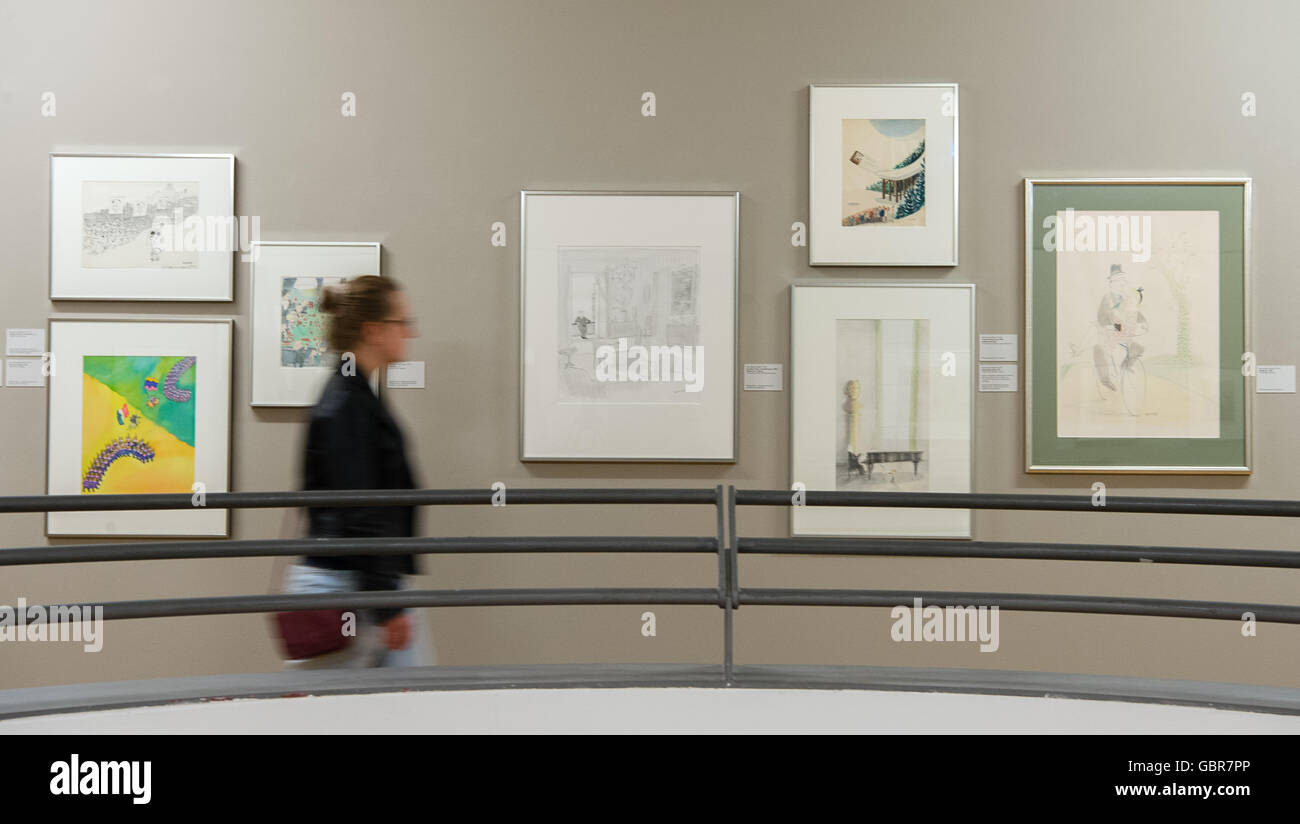 Hanover, Germany. 8th July, 2016. A woman walking past caricatures during a press conference on the opening of the Stock Photo