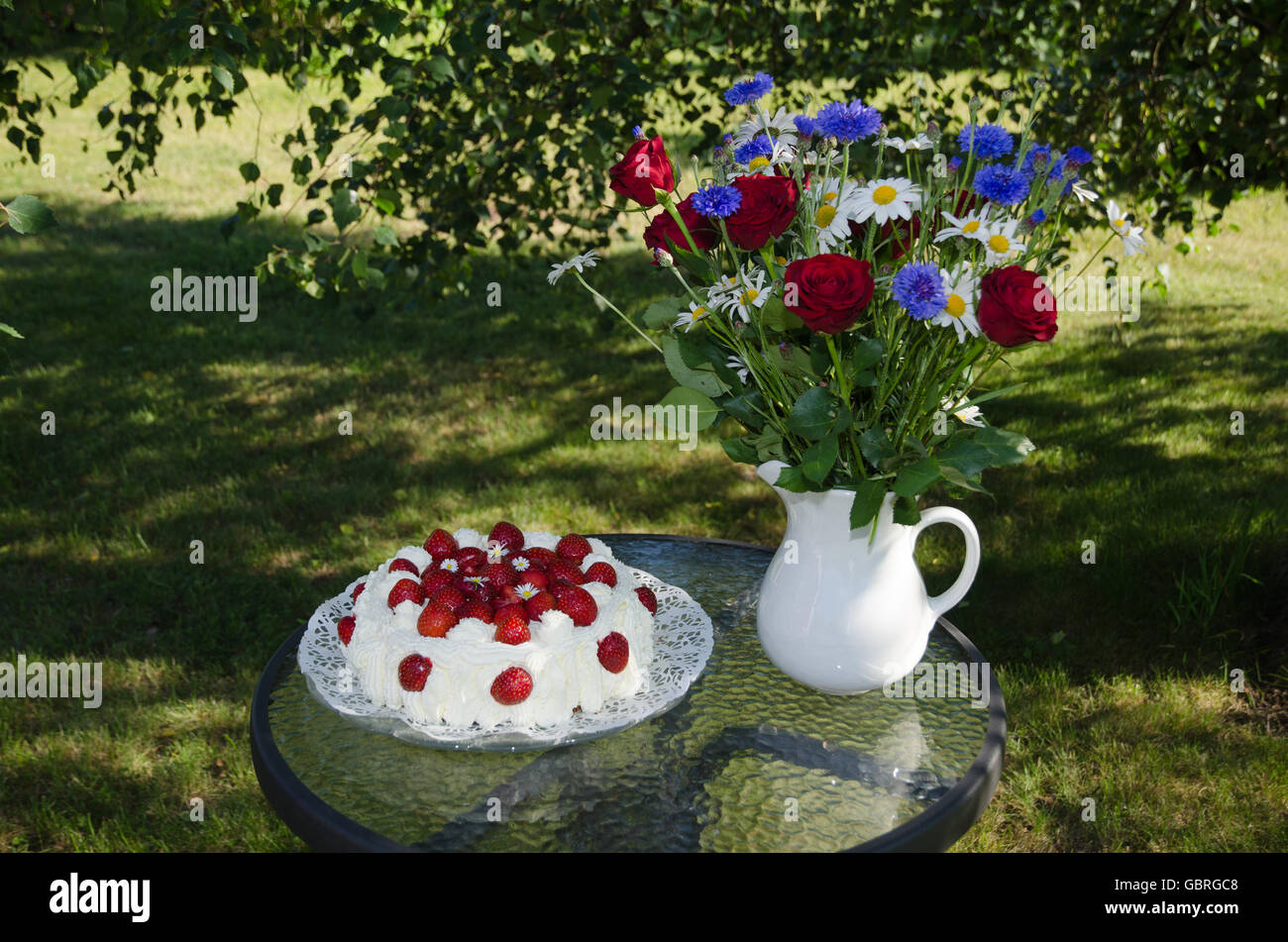 Strawberry cake an a bouquet of summer flowers on a table in a ...
