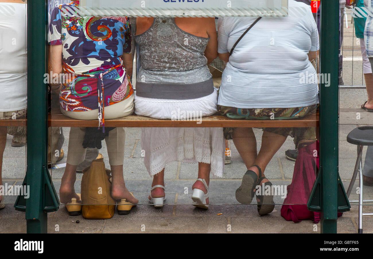 three women woman sitting bench seat bus shelter - Stock Image