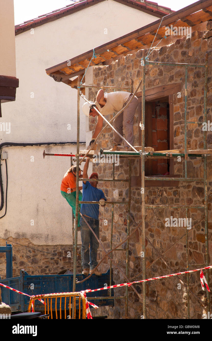 Builders working of scaffolding renovating a house in Potes Northern Spain - Stock Image