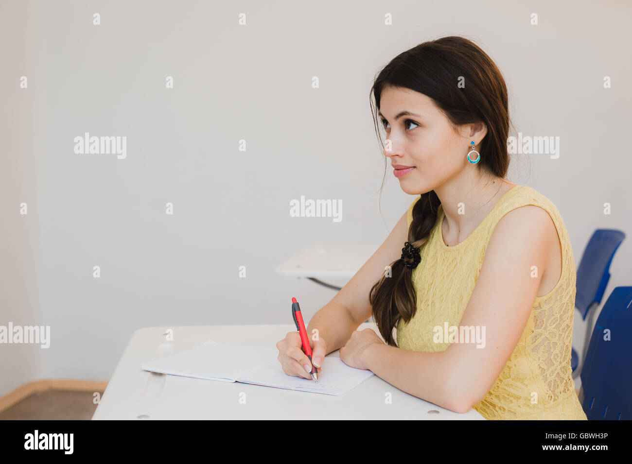 Female Teenage Student Studying In Classroom - Stock Image