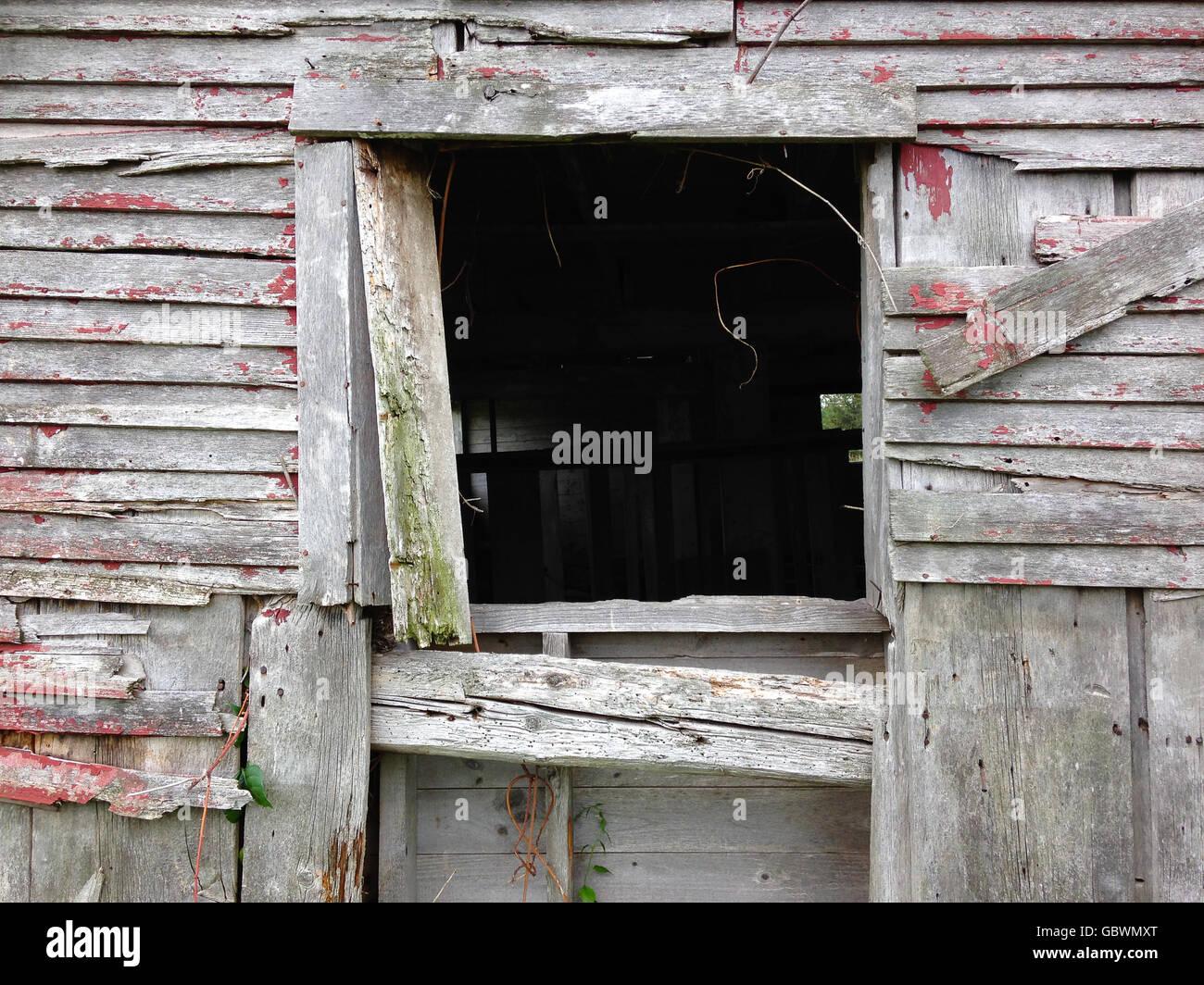 Window of an old, falling apart barn - Stock Image