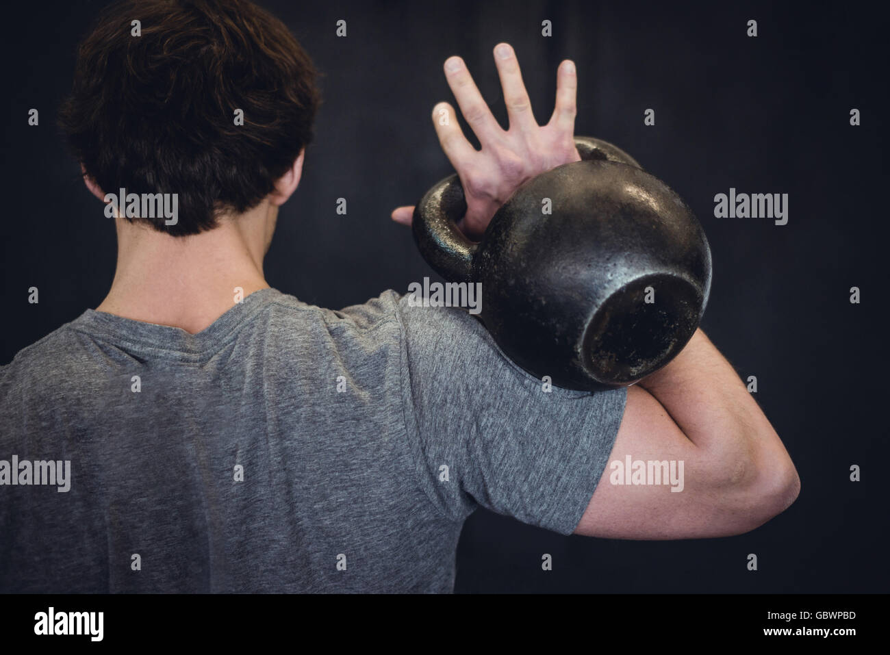Man working out in gym with kettlebell. - Stock Image