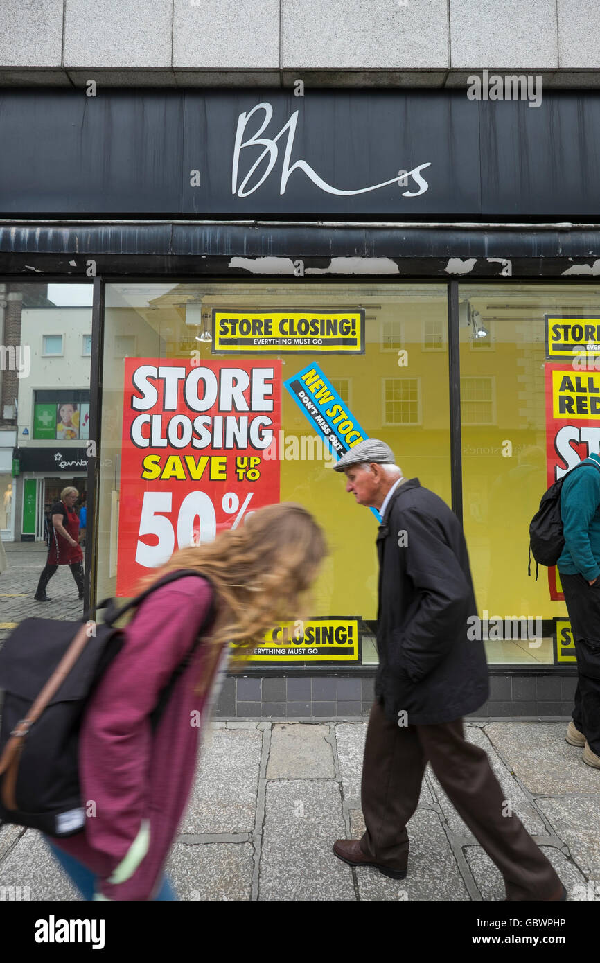 Shoppers passing British Home Stores shop in Truro, Cornwall, with closing down notices in the windows. - Stock Image
