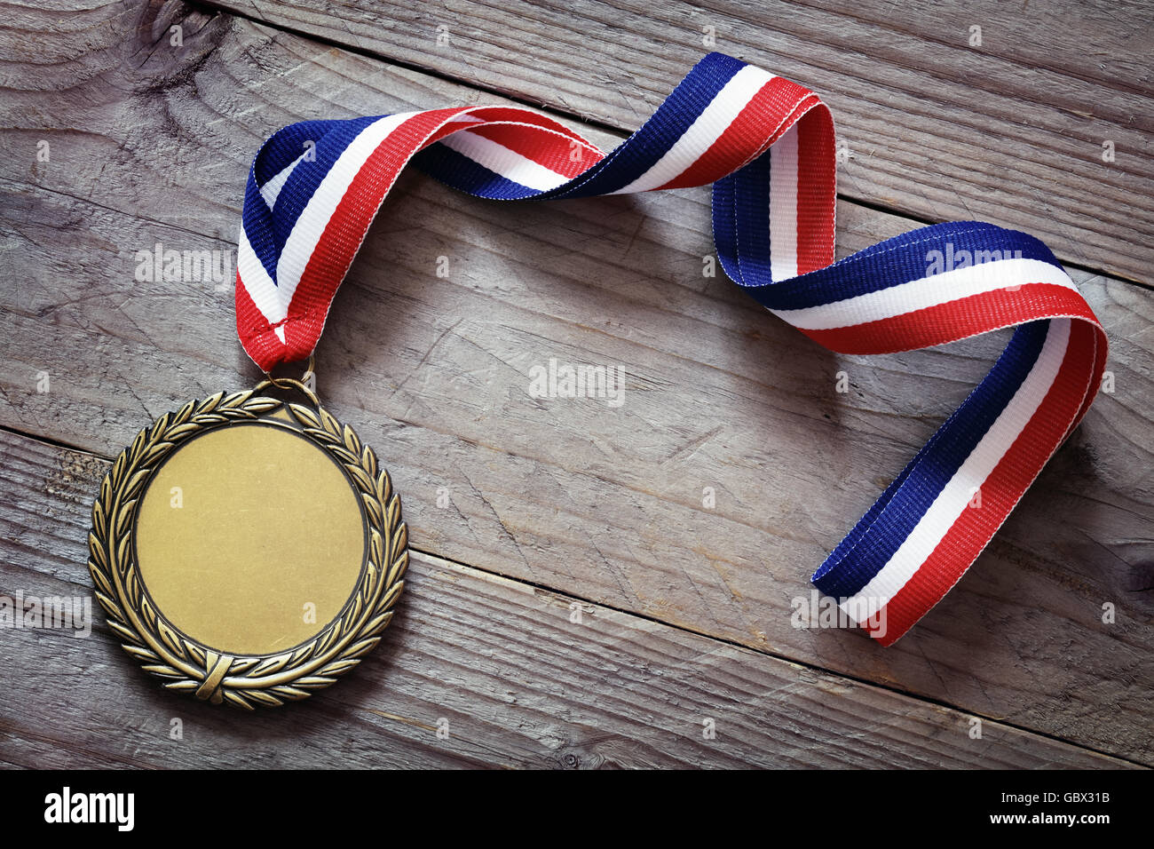 Gold medal on wood background with blank face for text, concept for winning or success - Stock Image