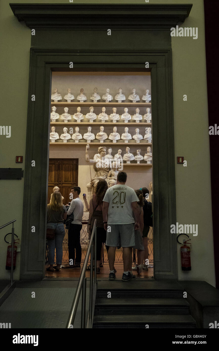 Tourists looking at the marble busts and statues in the room of the 19th century in the Galleria dell Academia in - Stock Image