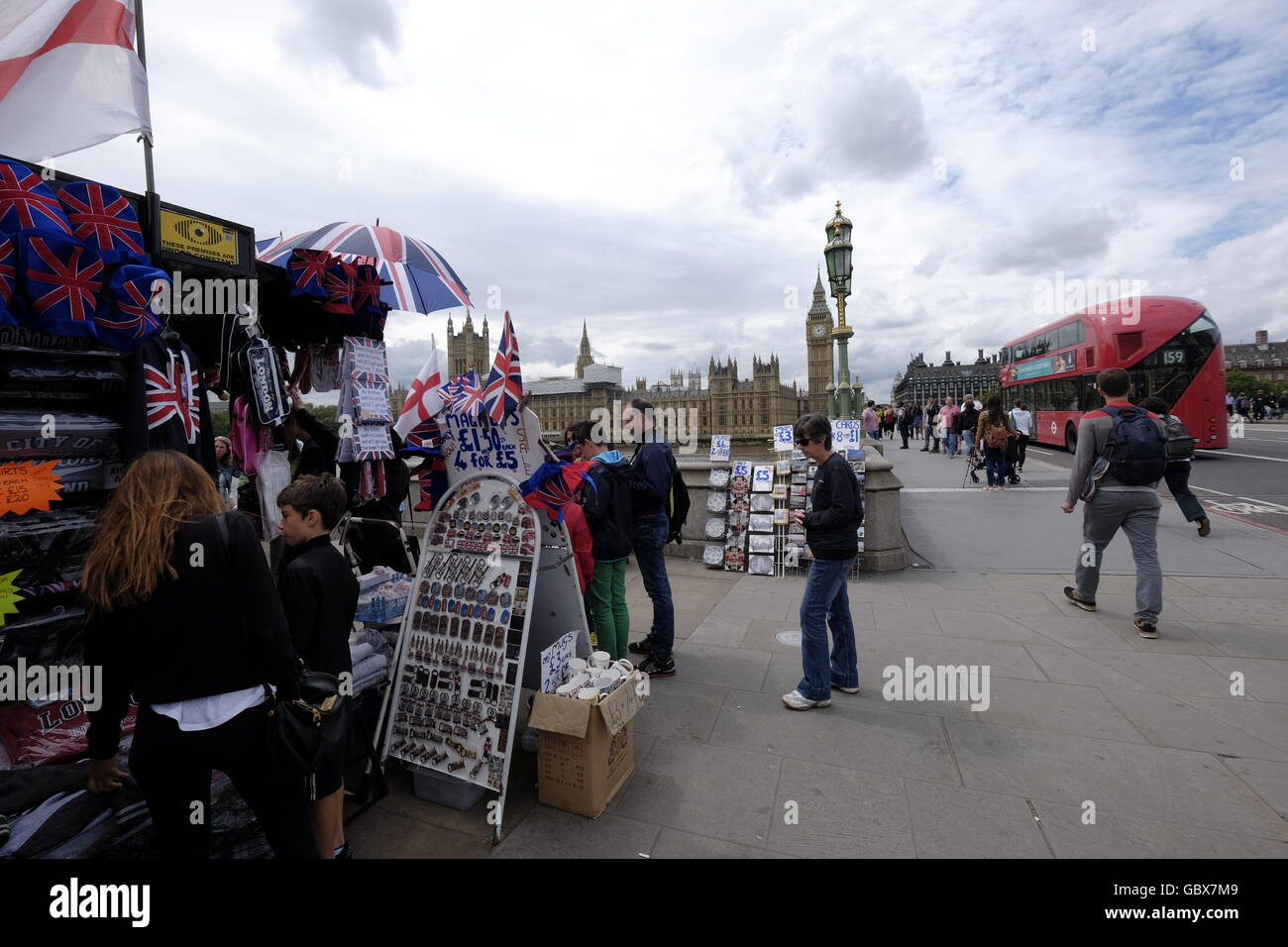 Curio sellers at their stall on Westminster Bridge with the Houses of Parliament and Big Ben in the background - Stock Image