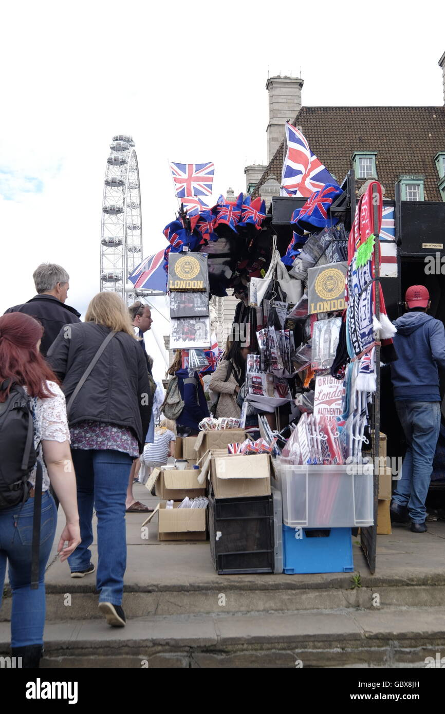 Curio sellers at their stall on Westminster Bridge with the London Eye in the background Stock Photo