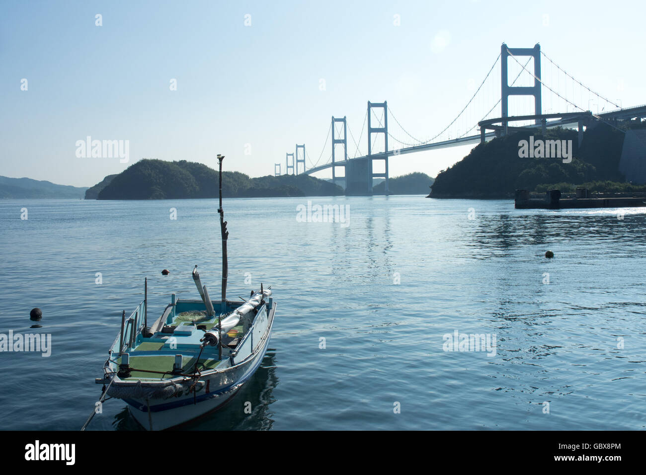 A wooden fishing boat moored in the Seto Inland Sea, and the Kurushima Kaikyo bridges in the background. - Stock Image