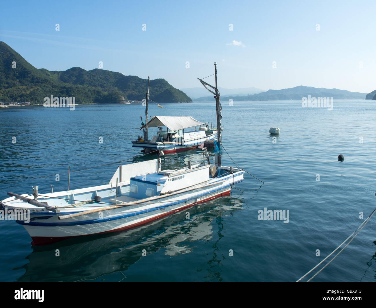 Two wooden fishing boats moored in the Seto Inland Sea. - Stock Image
