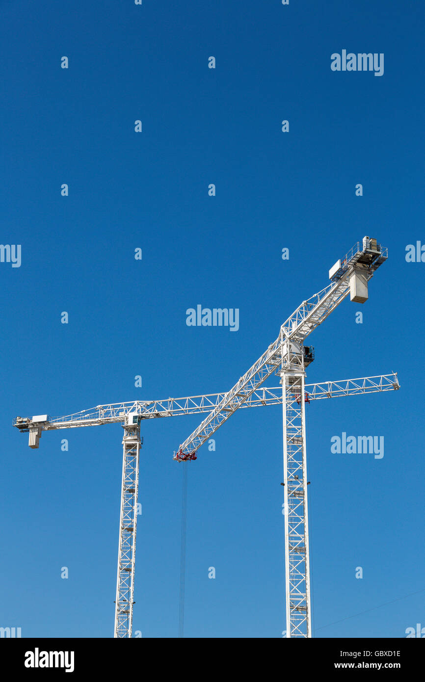 Two tower cranes work in London against blue sky - Stock Image