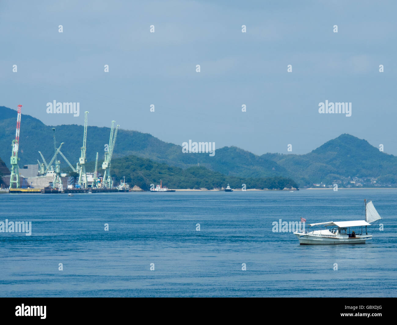 A small traditional Japanese fishing boat in the Seto Inland Sea and ship building facilities on the Innoshima Island. - Stock Image