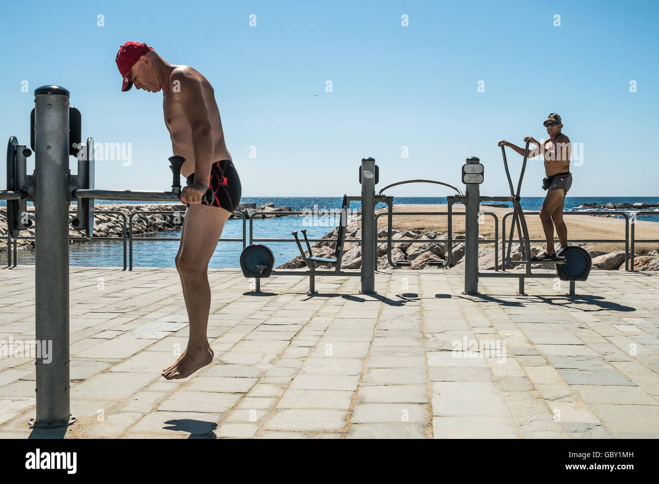 Two elderly men working out at the seaside in Barcelona, Spain. Stock Photo