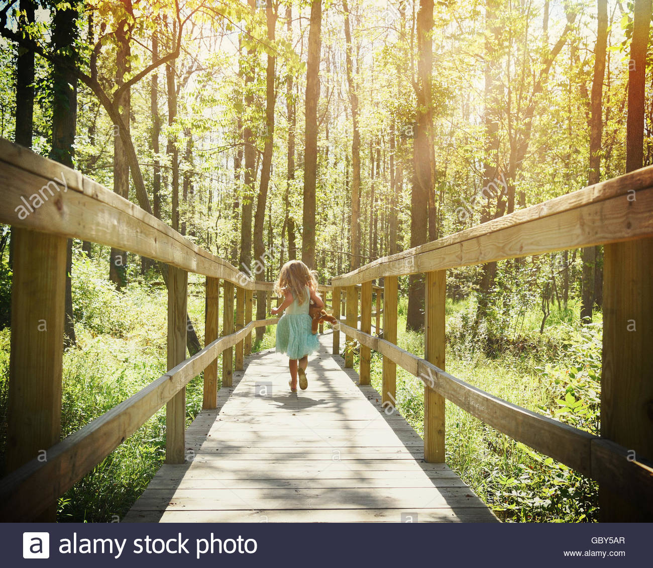 A little child is running on a wooden trail in the woods with trees with sunlight rays for a freedom or adventure - Stock Image
