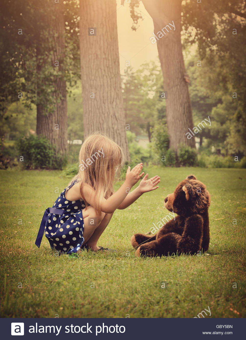 A little girl is clapping her hands and playing with a teddy bear outside at a park for a friendship or imagination - Stock Image