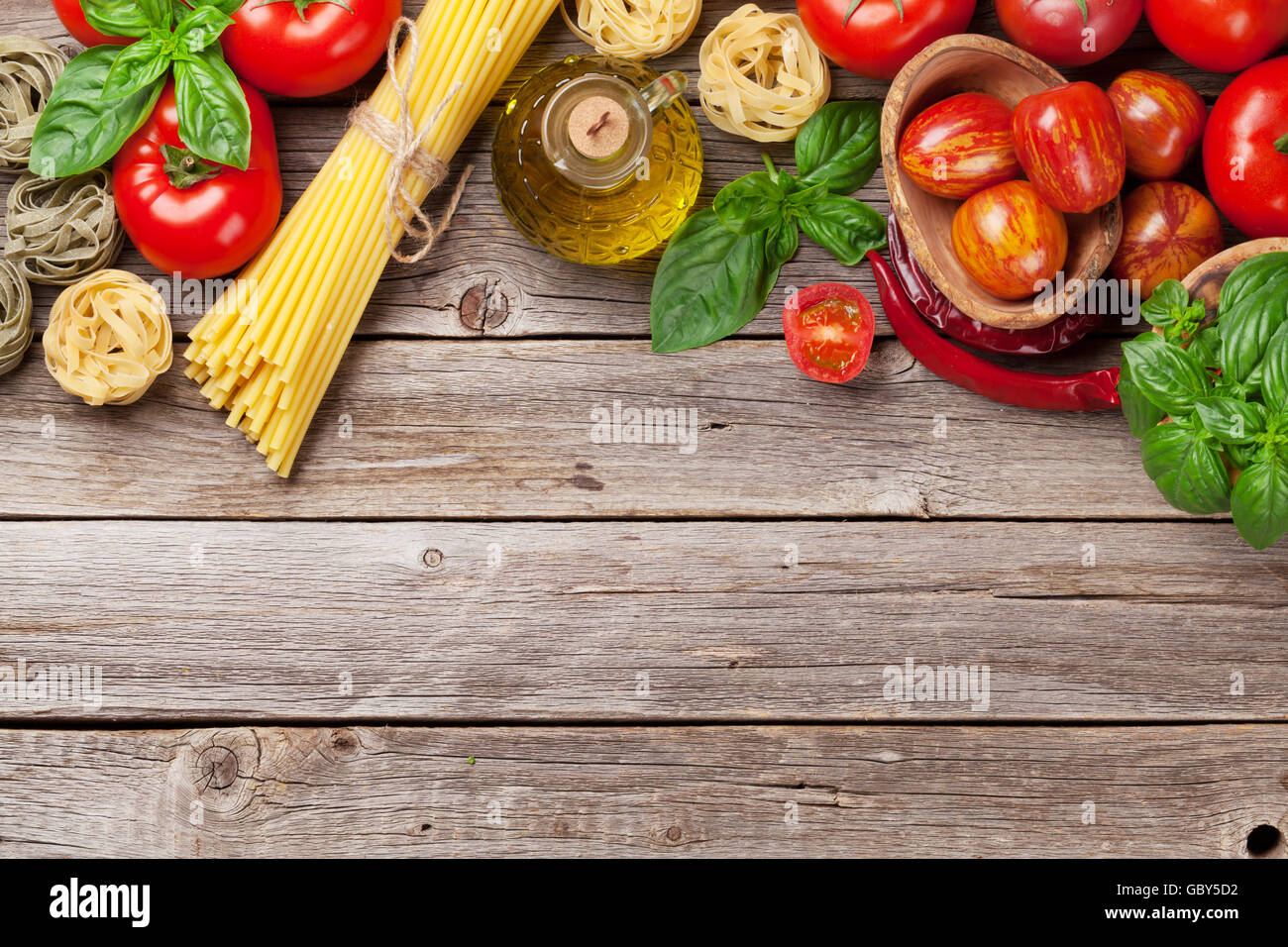 Italian food cooking. Tomatoes, basil, spaghetti pasta, olive oil and chili pepper on wooden kitchen table. Top Stock Photo