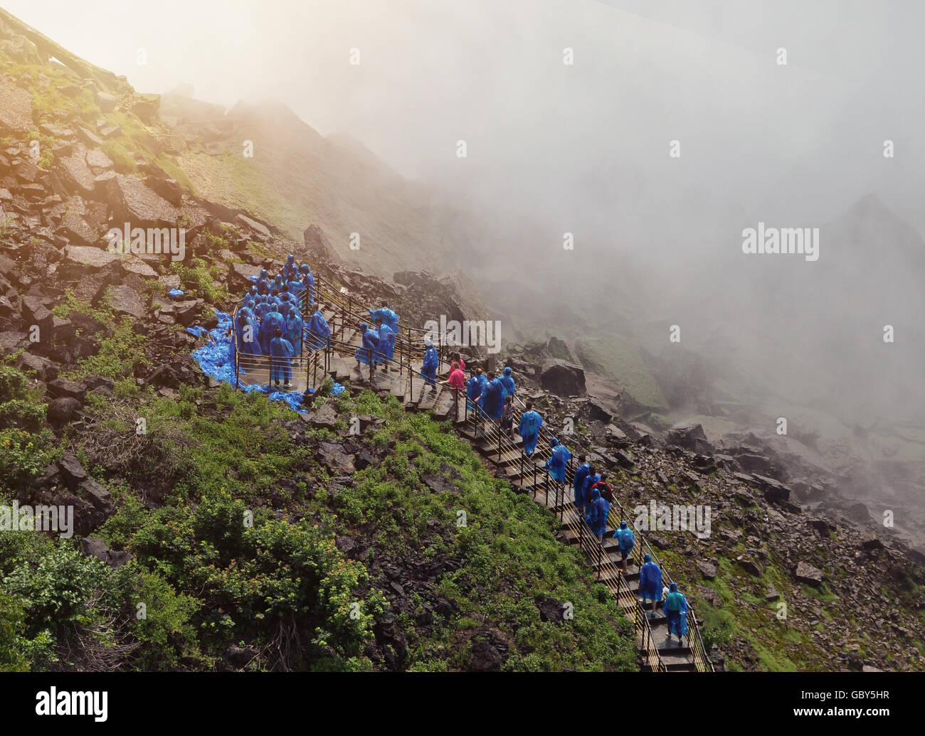 Tourists are walking up a stairway to Niagara Falls with wet water mist and blue raincoats on for a travel or nature - Stock Image