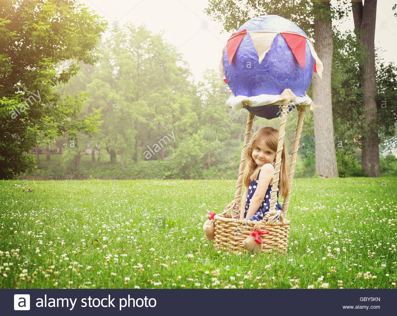 A child is sitting in a hot air balloon basket pretending to travel and fly  for a creativity or imagination concept. - Stock Image