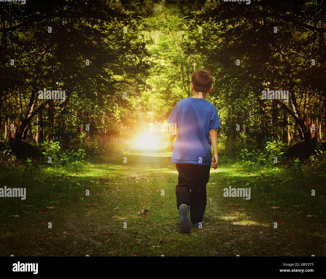 A child is walking in the dark woods into a bright light on a path for a freedom or happiness concept. Stock Photo