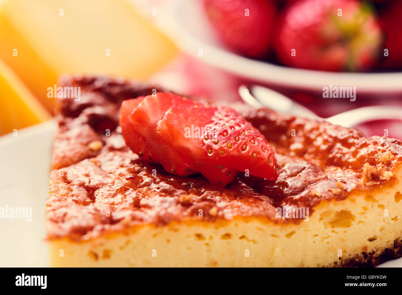 closeup of a plate with a piece of homemade cheesecake topped with sliced strawberries on a set table - Stock Image
