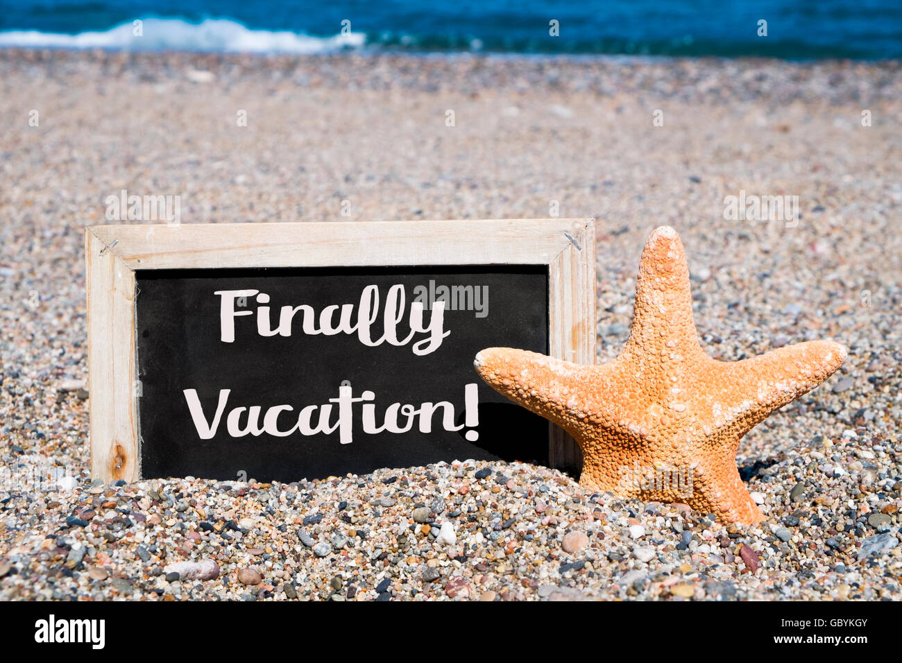 closeup of a starfish and a wooden-framed chalkboard with the text finally vacation written in it, placed on the Stock Photo