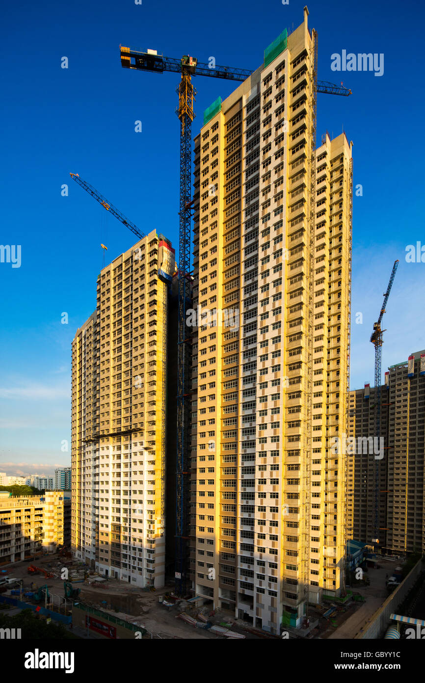Tall houses in construction under the blue sky during sunset timing - Stock Image