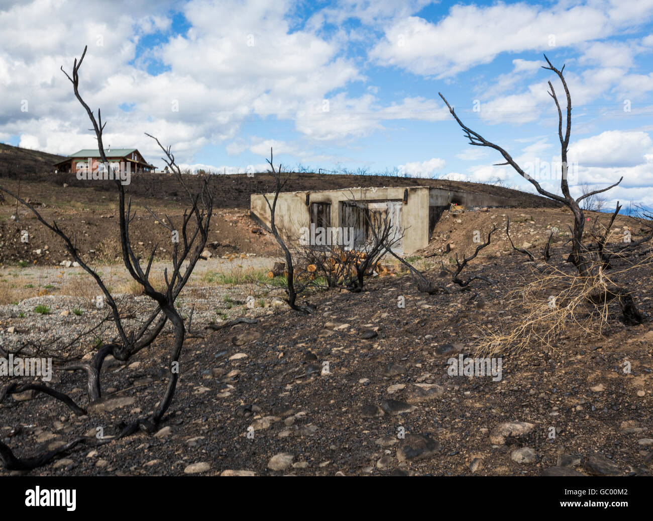 Remains of a burned house home in charred rural landscape after a fire. Destruction caused by natural disaster wildfire. - Stock Image