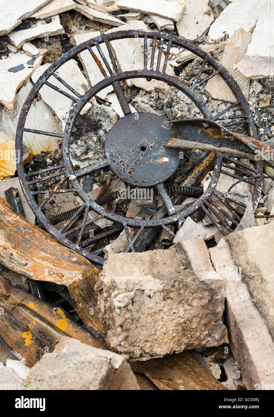 Destroyed personal property after a house fire. Clock in ruins of burned home after a natural disaster wildfire. - Stock Image